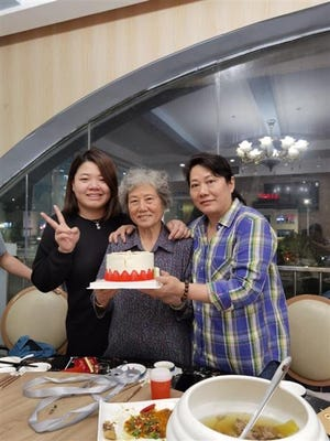 "Xiaojie ""Emily"" Tan's family in China celebrated what would have been her 50th birthday this week. Tan's mother, center, had not been told of her daughter's death because family members were worried it would make her sick."