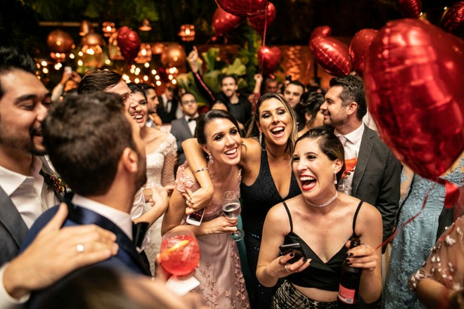 Groom and wedding guests laughing during their party.