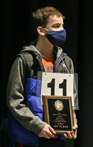 Andrew Yeager form Chippewa High School holds his trophy after winning the Akron Beacon Journal Regional Spelling Bee on Saturday at Hudson Middle School.