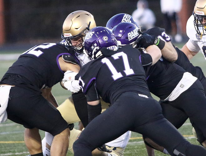 Mount Union defenders bring down John Carroll running back Matthew Buser during the Purple Raiders' game against John Carroll Friday, March 19, 2021 at Mount Union Stadium.