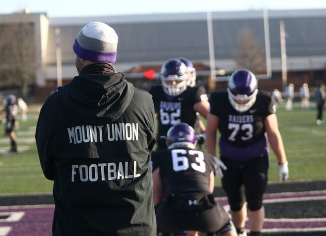 Mount Union head football coach Geoff Dartt, left, watches his team warm up before a game against John Carroll\, March 19, 2021 at Mount Union Stadium.