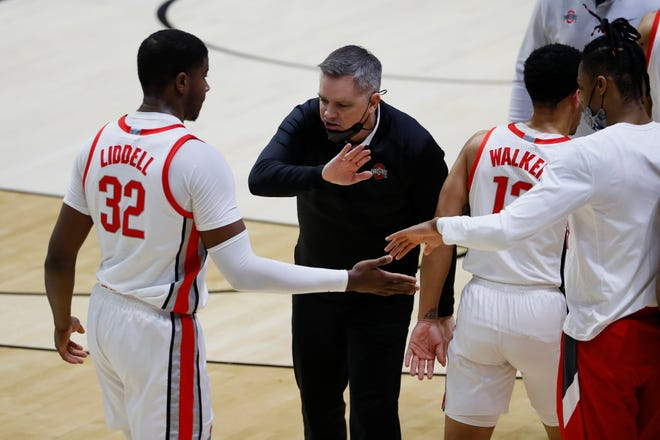 Mar 19, 2021; West Lafayette, Indiana, USA; Ohio State Buckeyes forward E.J. Liddell (32) is greeted by head coach Chris Holtmann during a time out in the first half against the Oral Roberts Golden Eagles in the first round of the 2021 NCAA Tournament at Mackey Arena. Mandatory Credit: Joshua Bickel-USA TODAY Sports