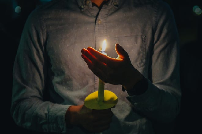 A student holds a candle during a vigil last Friday night on the University of Missouri campus to honor the victims of the March 16 Atlanta shootings.