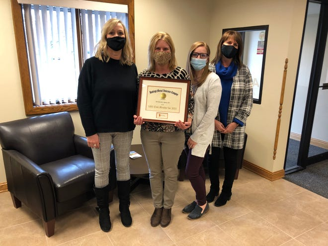 From left, Kris Nowicki, Deb Wright, Kaylyne Ryan and Lori Briggs, team members of Iott Insurance Agency's Petersburg location, stand with the award the agency received in February for being named to Hastings Mutual's 1885 Club. Iott Insurance Agency also has offices in Lambertville and Blissfield.