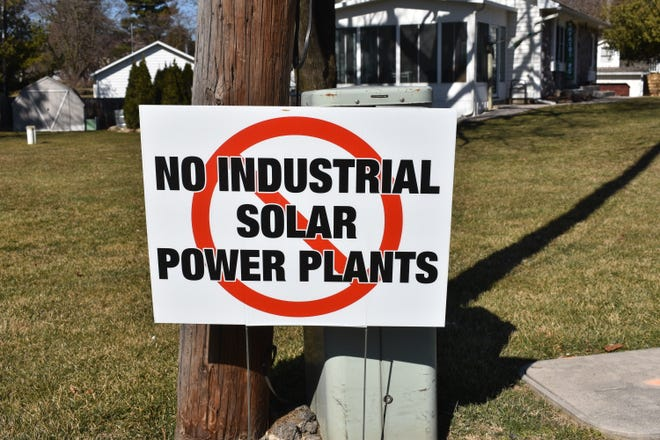 Signs like this one at the intersection of Macon Highway and Clinton-Macon Road against a proposed solar power plant have been scattered throughout Macon Township in recent weeks.