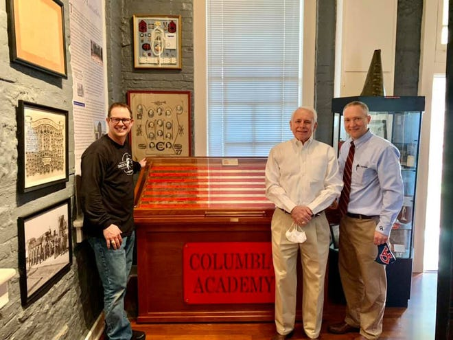Eric Dotson of Smokin' Chisel, left, Ronnie Erwin, center, Dr. James Thomas, attend the unveiling of the new class ring display at Columbia Academy.