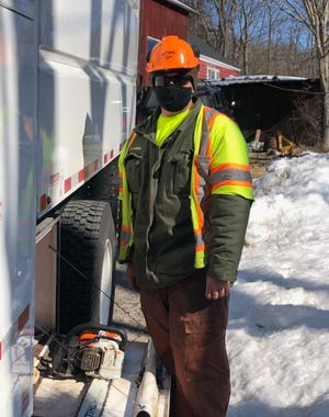 Anthony Larkin stands next to a truck while wearing safety gear at the Delaware Water Gap National Recreation Area.
