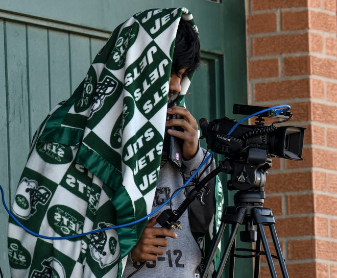 Alan Chairez tries to keep warm with a blanket over him while video taping the Garden City Community College baseball game at Williams Stadium. Although it was a spring sporting event, temperatures were more like a chilly late-winter game with a brisk wind.