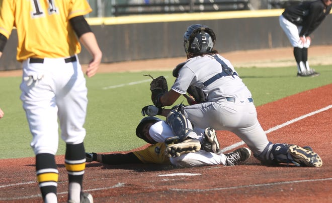 Rogers State's Jonathan Soto applies the tag on FHSU's Ed Scott before he can touch home. The out ended the game.