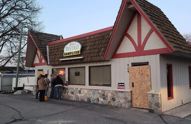 Volunteers corrected signage at Marlena's Bistro and Pizzeria on Friday, March 19, to indicate the business was closed. While signs were in place and doors boarded, caution and neon tape which had been placed earlier were removed from the building.