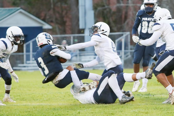 Northside's David Jefferson (9) helps bring down Swansboro's Damien Flores in the Monarchs' 21-7 win Friday night.