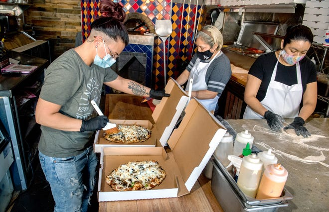 Nikki Zuccarini, left, general manager of Sugar Wood-Fired Bistro, and staff members Robertina Velazquez, middle, and Milagros Montesinos prepare pizzas to go at the popular Warehouse District restaurant at 826 SW Adams St. in Peoria. Although Sugar is arguable best known for its wood-fired pizza, its best-selling carryout item is the roasted salmon salad.