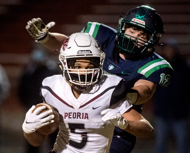 Peoria High running back Aziah Fisher (5) escapes a Peoria Notre Dame defender in the second half Friday, March 19, 2021 at Peoria Stadium. The Lions defeated the Irish 62-49.