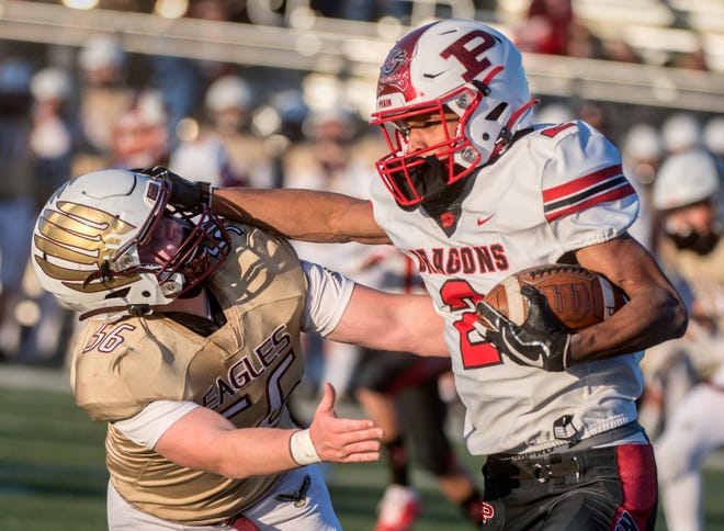 Pekin running back Kanye Tyler, right, fends off Dunlap's Ryan Schuck in the first half Friday, March 19, 2021 in Dunlap.