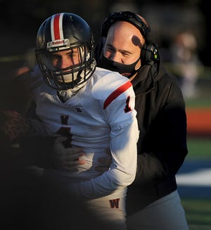 Wellesley High School football senior Anthony Perez gets a hug from head coach Jesse Davis (right) after scoring at Needham, March 19, 2021. Perez scored two touchdowns and had over 160 receiving yards in a win over Weymouth Thursday night.