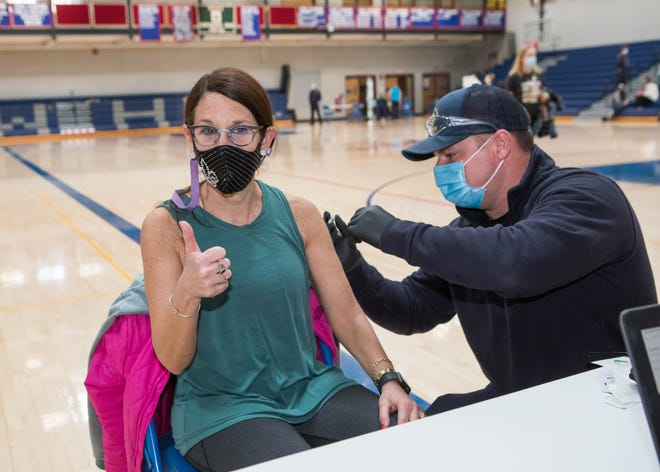 """SAU 90 Superintendent Lois Costa gives a """"thumbs up"""" and was happy that she was able to get her first shot of the Moderna COVID-19 vaccine as Hampton Fire and Rescue's Damien Sevin administers the shot at Winnacunnet High School in Hampton on Saturday. [Matt Parker/Seacoastonline.com]"""