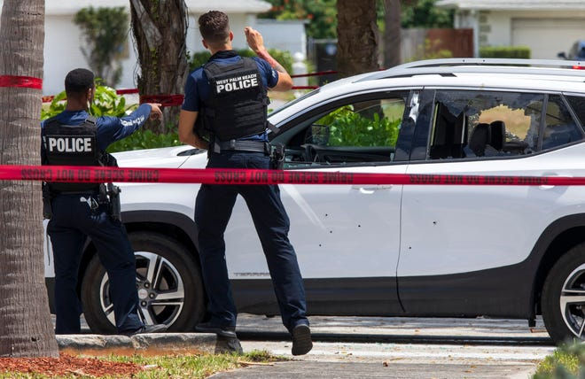 West Palm Beach police examine a car with shot-out windows and riddled with bullet holes as they investigate a shooting Saturday in the parking lot of the Home Depot on Palm Beach Lakes Boulevard. Two men injured in the shootout have been released from the hospital, city police said Sunday.