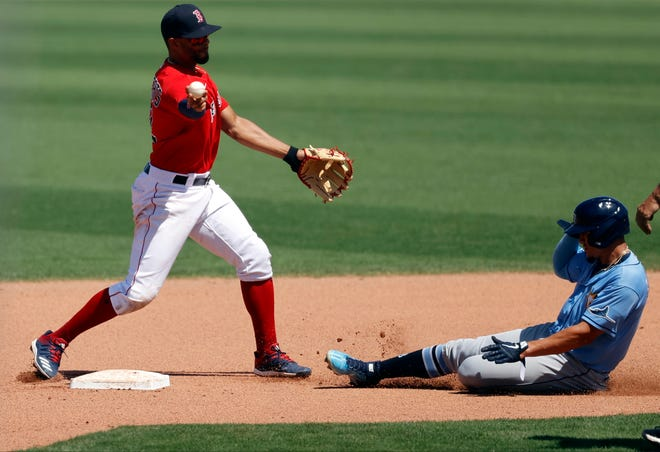 Boston Red Sox shortstop Xander Bogaerts (left) forces out Tampa Bay Rays shortstop Willy Adames and throws the ball to first base for an out during the fifth inning at JetBlue Park at Fenway South on Friday.