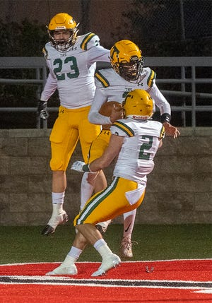 Tracy's Noah Deneau, center, celebrates his touchdown with teammates Tommy Chavez, left, and Jacob Strout during a varsity football game March 19 at Lincoln's Spanos Stadium in Stockton.