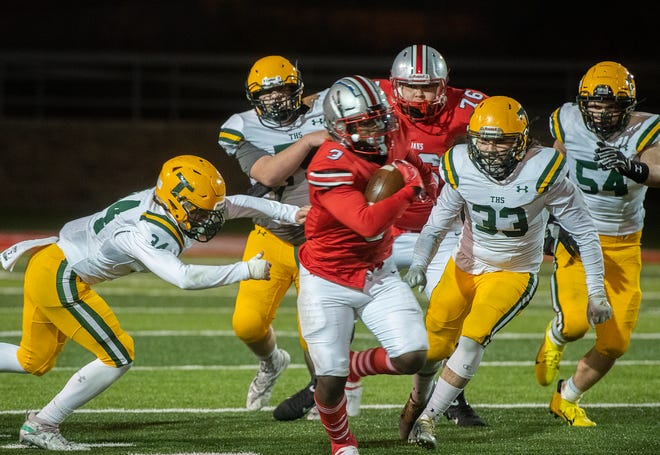 Lincoln's Jonah Coleman, center, escapes from a group of Tracy defenders during a varsity football game at Lincoln's Spanos Stadium in Stockton.