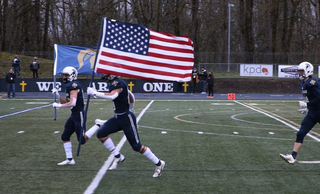 Marist football players take the field for their game against Silverton in Eugene Friday March 19, 2021.
