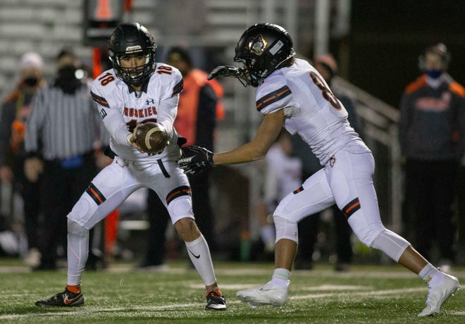 Harlem quarterback James Cooper, Jr., shown handing off to Deandre Young in a season-opening win over Auburn, passed for 440 yards last week against Belvidere North, second-most in NIC-10 history, and has committed to Iowa Western Community College.