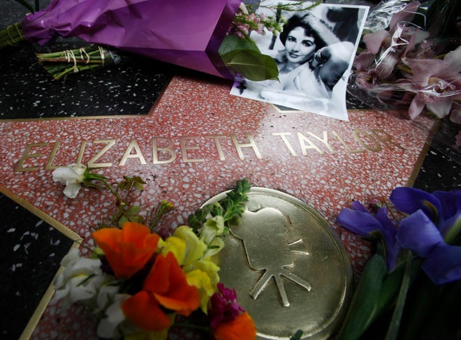 Flowers and a portrait adorn Elizabeth Taylor's star on the Hollywood Walk of Fame in Los Angeles on March 23, 2011. Taylor died early March 23 of congestive heart failure at the age of 79.