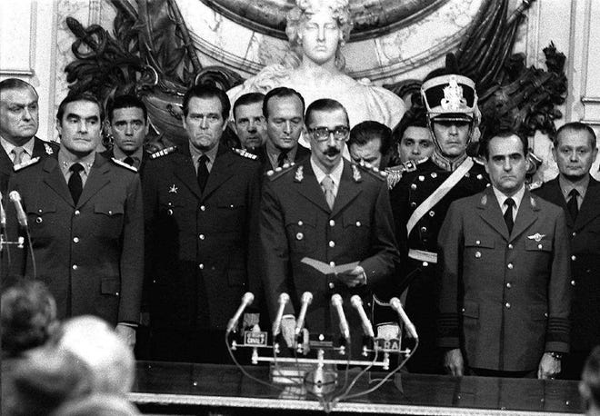 FILE - In this March 24, 1976 file photo, Gen. Jorge Rafael Videla, center, is sworn-in as president at the Buenos Aires Government House accompanied by Adm. Emilio Massera, second from left, and Brig. Orlando Agosti, second from right, members of the junta that overthrew President Isabel Peron.