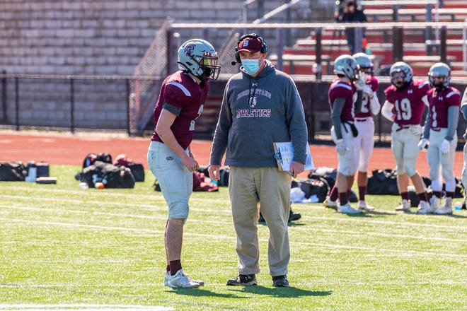 Bishop Stang head coach Dennis Golden gives the play to Spartans quarterback Dylan Aguiar earlier this season against Archbishop Williams.