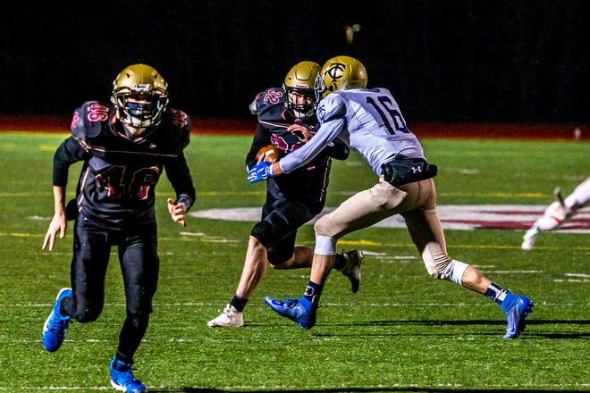 Old Colony's Ryan McGuiggan looks to power his way through Tri-County's Peter McEnaney earlier this season. On Friday, McGuiggan scored on a one-yard run as time expired to lift the Cougars to their first win of the season.