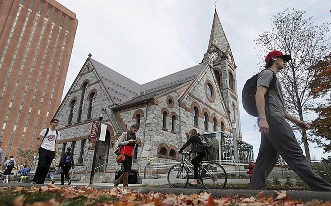 Students pass the Old Chapel at the University of Massachusetts campus in Amherst.