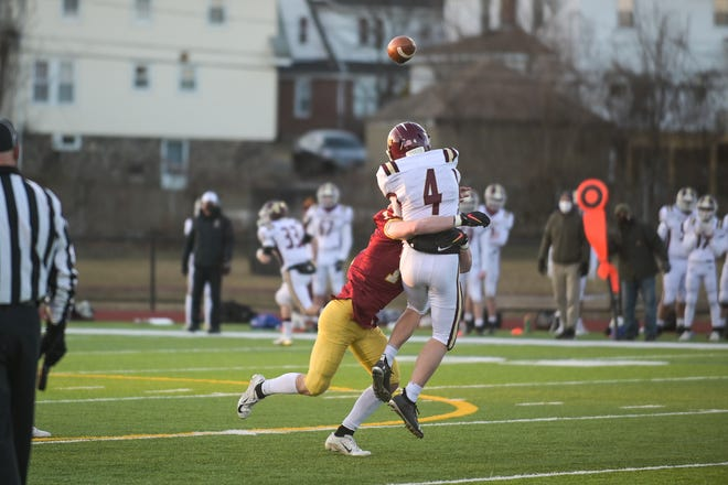 Algonquin quarterback Jeff Valentine gets a pass off before getting racked by Doherty's Thomas Murray.