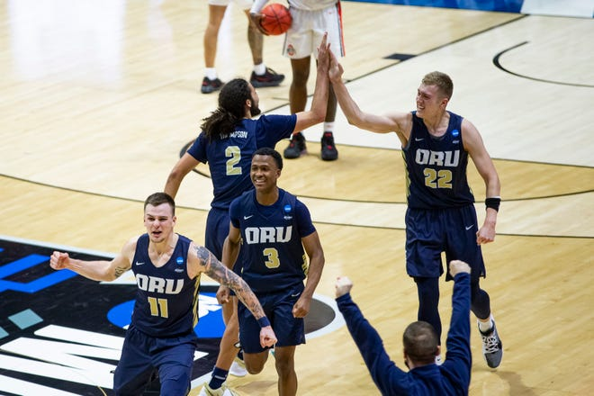 Oral Roberts players celebrate after beating Ohio State in a first-round game Friday of the NCAA men's college basketball tournament at Mackey Arena in West Lafayette, Ind.