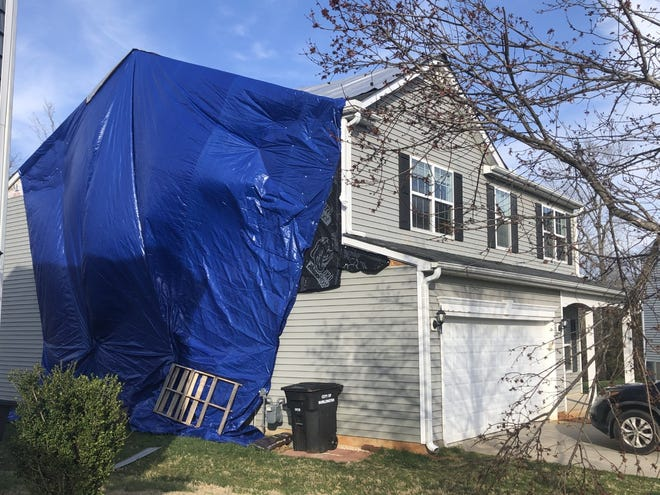 Many tarps cover roofs or portions or houses in a neighborhood off Springwood Church Road in Burlington that was hit by Thursday's tornado.