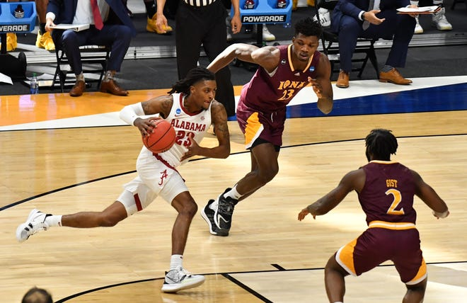 Mar 20, 2021; Indianapolis, Indiana, USA; Alabama Crimson Tide guard John Petty Jr. (23) drives the lane against Iona Gaels forward Nelly Junior Joseph (23) and guard Asante Gist (2) during the first round of the 2021 NCAA Tournament at Hinkle Fieldhouse. Mandatory Credit: Patrick Gorski-USA TODAY Sports