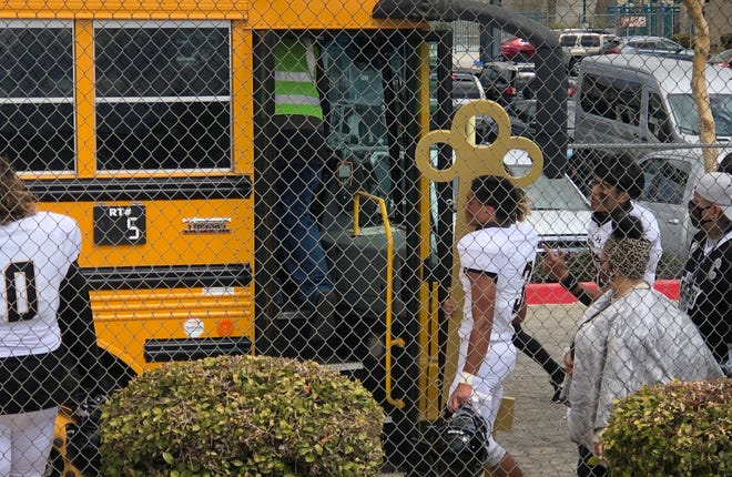 Hesperia's Adam Rodriguez, center, carries the Key back onto the team's bus after beating Sultana 28-0 on Saturday, March 20, 2021.