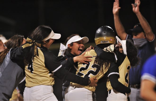 Abilene High players swarm KK Roberson (22) after Roberson's two-out, RBI single capped a sixth-run seventh inning to lift the Lady Eagles to an 8-7 victory over Wolfforth Frenship in the District 2-6A game Friday at AHS.