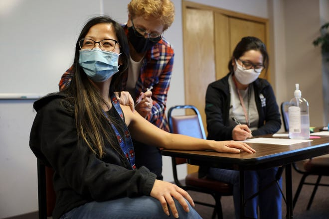 "Lisa Xiong, a staff member at The Hmong Institute, gets her first dose of the Moderna COVID-19 vaccine at a clinic at Life Center in Madison, Wis., on March 9, 2021. ""It wasn't as bad as I thought,"" she said after Laurel Losenegger, a volunteer nurse with the Benevolent Specialists Project, delivered the shot."