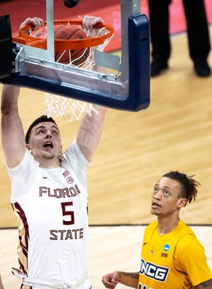 Florida State center Balsa Koprivica (5) dunks the ball over UNC Greensboro guard Kaleb Hunter (44) during the first round of the 2021 NCAA Tournament on Saturday, March 20, 2021, at Bankers Life Fieldhouse in Indianapolis, Ind.