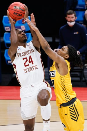 Florida State guard Sardaar Calhoun (24) attempts to shoot the ball over UNC Greensboro guard Keyshaun Langley (0) during the first round of the 2021 NCAA Tournament on Saturday, March 20, 2021, at Bankers Life Fieldhouse in Indianapolis, Ind.