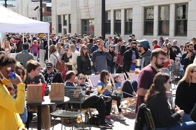 People gather for a viewing party for the NCAA March Madness Championship on Saturday, March 20, 2021, at the newly opened Bottleworks District in Indianapolis.  The recreation area is built around the historic Coca Cola Bottling Factory, near the north end of Mass Ave.