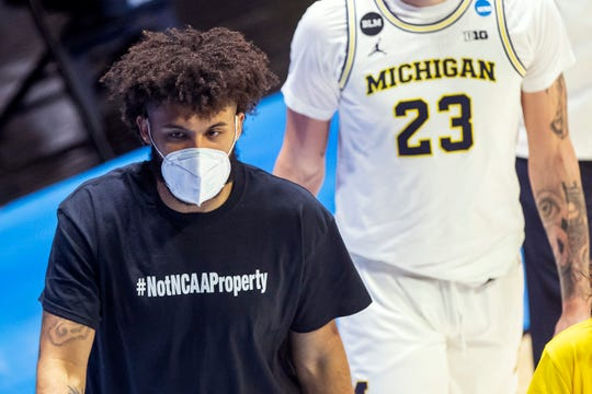 "Michigan's Isaiah Livers wears a T-shirt that reads ""#NotNCAAProperty"" as he walks off the court with teammates after the first half of a first-round game against Texas Southern in the NCAA men's college basketball tournament, Saturday, March 20, 2021, at Mackey Arena in West Lafayette, Ind."