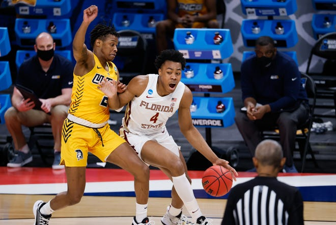 Florida State guard Scottie Barnes (4) dribbles the ball as UNC Greensboro guard AJ McGinnis (2) defends during the first round of the 2021 NCAA Tournament on Saturday, March 20, 2021, at Bankers Life Fieldhouse in Indianapolis, Ind.