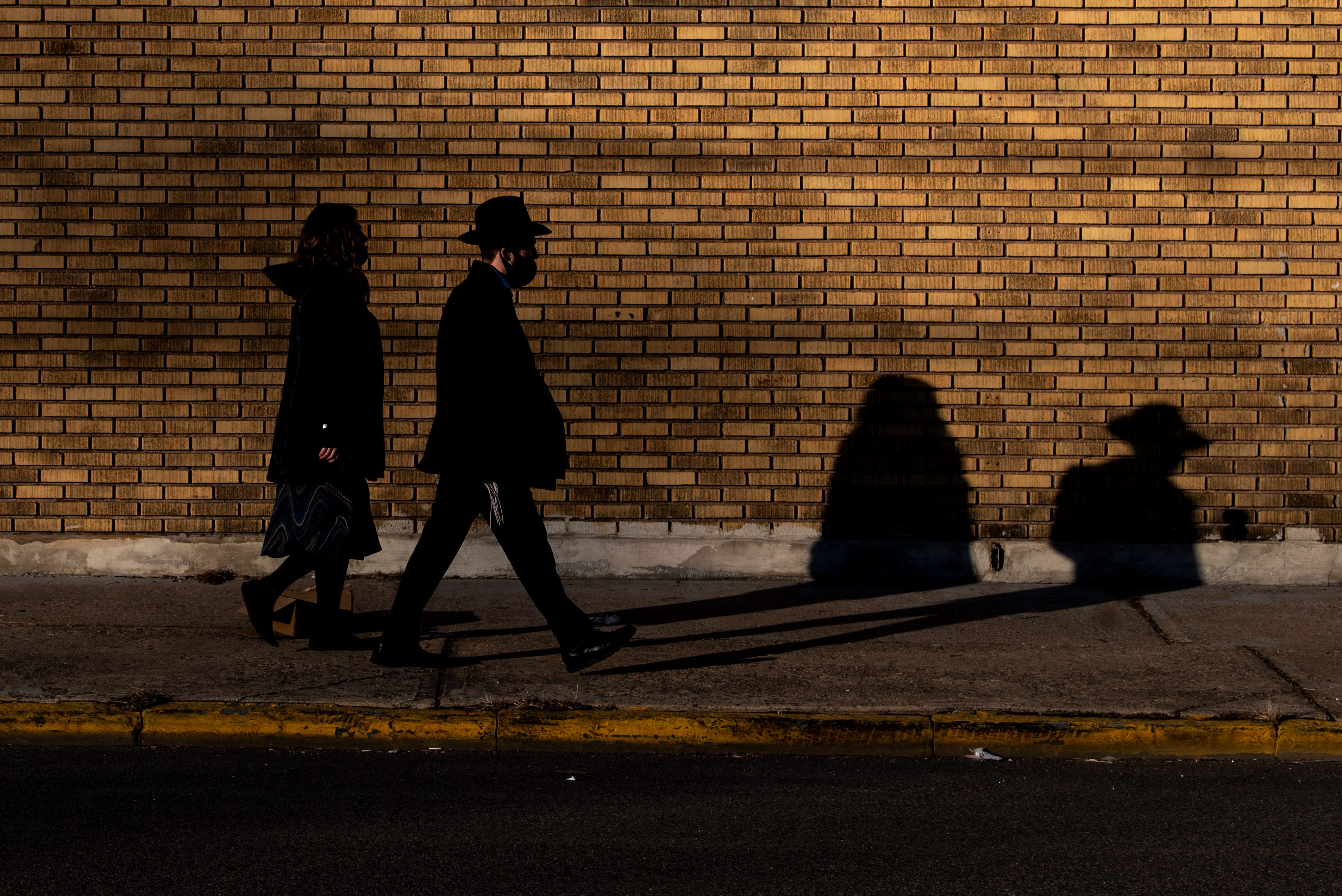 A young Jewish couple walks along Van Houten Avenue on Saturday, March 20, 2021. Passaic has a large Orthodox Jewish community and houses 20 Orthodox synagogues.