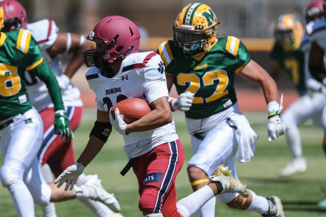 Jordan Cabellero (32) runs the ball as the Mayfield Trojans take on the Deming Wildcats at the Field of Dreams in Las Cruces on Saturday, March 20, 2021.