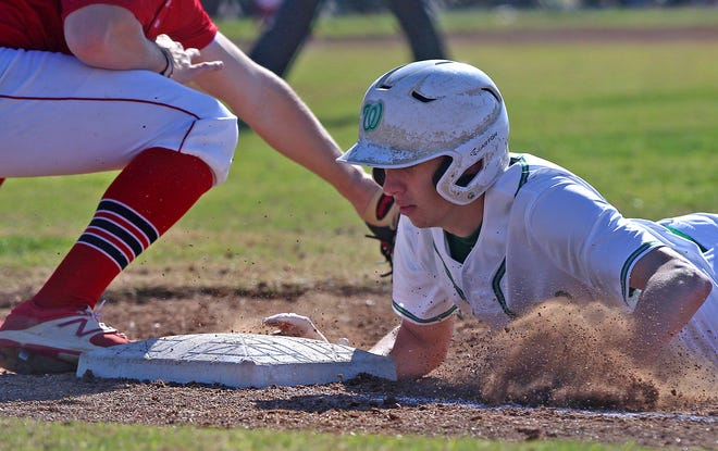 Austin Williams dives back to first base for Wall during a game against Jim Ned on Friday, March 19, 2021.