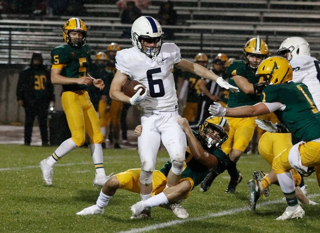 Central Valley Christian's Ethan Hansen picks up a big gain against Kingsburg during the first half of their football game in Kingsburg, Calif. Friday, March 19, 2021.