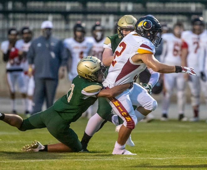 Tulare Union's Josh Rodriguez gains yardage as Garces' Jalani Smith tackles during the first half Friday night.