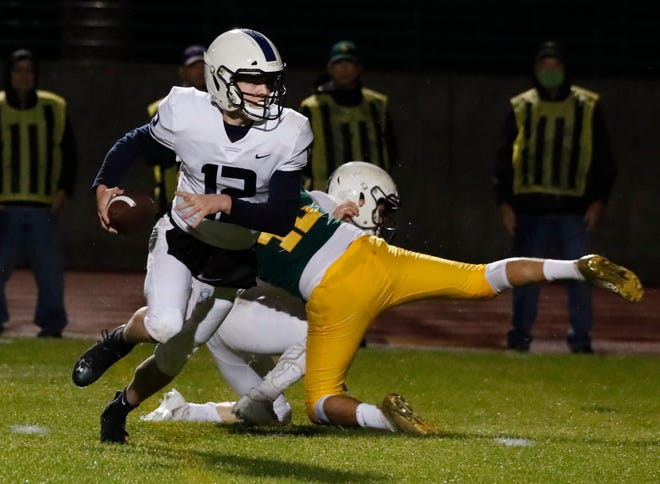 Central Valley Christian's quarterback, Max Bakker, heads downfield against Kingsburg during the first half of their football game in Kingsburg, Calif. Friday, March 19, 2021.