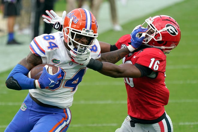 Gators tight end Kyle Pitts tries to fend off Georgia defensive back Lewis Cine.